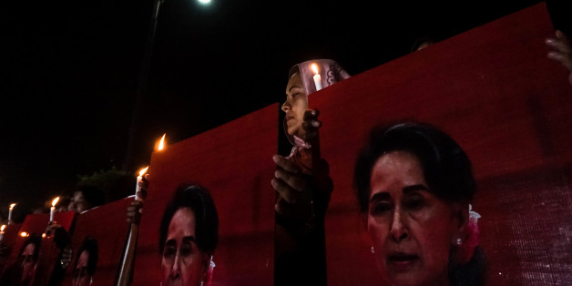 A muslim woman holds candles and portraits of Myanmar's State Counsellor and civilian leader Aung San Suu Kyi during the Interreligious Gathering of Prayer for Peace ceremony in Yangon on October 17, 2017. People attended in Yangon an interfaith rally on October 17, to show unity in a country seared by ethnically-charged violence against the Muslim Rohingya on its western border. Buddhist monks, Christian nuns, Hindus and Muslims were among those who joined the gathering in a display of support