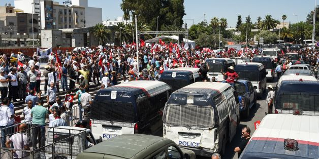 Members of the Tunisian security forces block the road with vehicles along Bardo Square, outside parliament in the capital Tunis on July 6, 2017, calling for the acceleration of the adoption of a law to protect policemen, following the latest attacks against their agents.A Tunisian policeman died on July 1, 2017 from severe burns sustained earlier the week prior when he was hit by a molotov cocktail during clashes in the central Sidi Bouzid region, according to an Interior Ministry statement. /