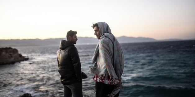 Young men look towards the Greek Chios island as they wait for the wind to calm down to travel on a dinghy with other migrants and refugees from Cesme in the Turkish province of Izmir on November 3, 2015. Amnesty International criticised Europe's failure to stop migrant deaths in the Aegean Sea as the death toll from ramshackle boats sinking off Greece rises daily. The group said over 450 refugees and migrants had died or gone missing in successive Aegean Sea sinkings in the first 10 months of t