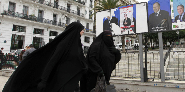 Algerian women walk past electoral posters in Algiers, April 2, 2014. Campaigning began on March 23 for an Algerian presidential election widely seen as a one-horse race that will ensure President Abdelaziz Bouteflika's a fourth term. REUTERS/Louafi Larbi  (ALGERIA - Tags: POLITICS SOCIETY ELECTIONS)