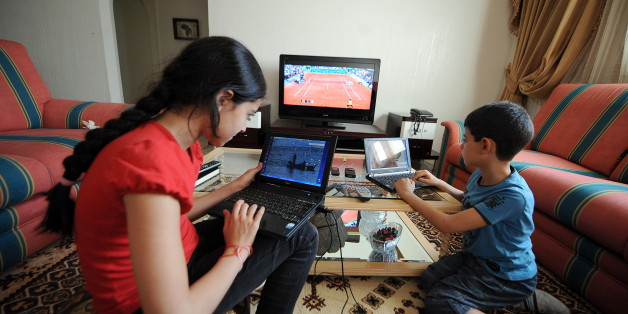 10 year old Nour(L)  and her brother Khalil(R) pose with their PC laptops at home, on May 25, 2010 in Tunis. AFP PHOTO : FETHI BELAID (Photo credit should read FETHI BELAID/AFP/Getty Images)