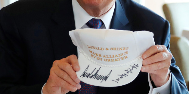 """U.S. President Donald Trump holds a hat he and Japan's Prime Minister Shinzo Abe signed, reading """"Donald & Shinzo Make Alliance Even Greater"""" before lunch and a round of golf at Kasumigaseki Country Club in Kawagoe, Japan November 5, 2017. REUTERS/Jonathan Ernst"""