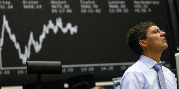A trader works at his desk in front of the German share price index, DAX board, at the stock exchange in Frankfurt, Germany, January 21, 2016.  European shares and oil prices held steady at multi-year lows on Thursday after a torrid two days that has wiped trillions of dollars off global markets. REUTERS/Kai Pfaffenbach