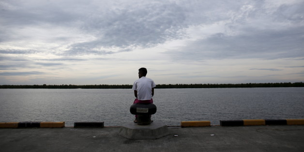 A Bangladeshi migrant who arrived recently by boat sits on a dock near a temporary shelter in Kuala Langsa, in Indonesia's Aceh Province May 25, 2015. Malaysia's police chief said on Monday that 139 graves believed to contain the remains of migrants were found near the country's border with Thailand, and that some graves contained more than one body. The graves were found at 28 suspected human trafficking camps located around 500 metres (550 yards) from the border in northern Malaysia, said Inspector General of Police Khalid Abu Bakar. REUTERS/Darren Whiteside