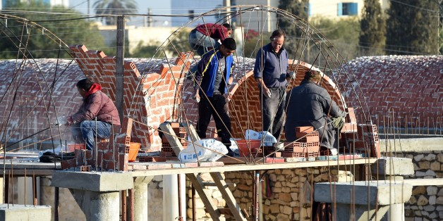 Tunisian builders work at the construction site of a new marketplace on December 15, 2015, in the impoverished central town of Sidi Bouzid, three days ahead of the fifth anniversary of the self-immolation of Mohamed Bouazizi, a young street vendor, which sparked the revolution that ousted a dictator and ignited the Arab Spring. Five years after triggering the Arab Spring, Tunisians doggedly pursue a democratic transition while other countries remain gripped by violence and repression.   AFP PHOT