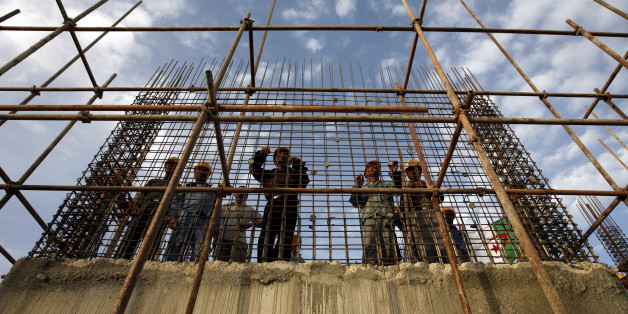 Chinese workers stands behind steel reinforcement at the construction site of a hospital during a visit by Algeria's President Abdelaziz Bouteflika to the city of Setif, 300km (186 miles) from Algiers June 25, 2007.  REUTERS/Zohra Bensemra (ALGERIA)