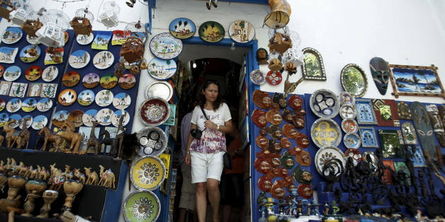 """A tourist walks out of a traditional souvenir shop in Sidi Bou Said, near Tunis, Tunisia July 7, 2015. Tunisian President Beji Caid Essebsi declared a state of emergency on Saturday, saying the Islamist militant attack on a beach hotel that killed 38 foreigners had left the country """"in a state of war"""".   REUTERS/Zoubeir Souissi"""