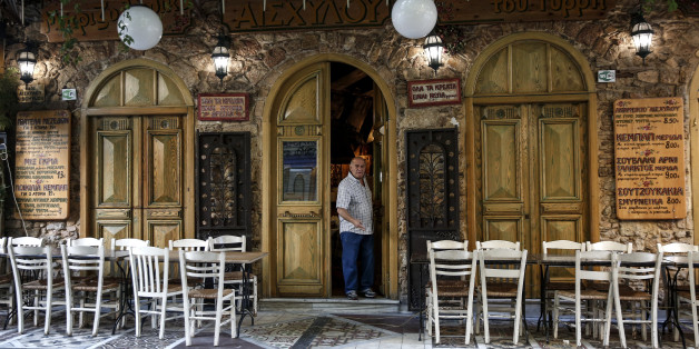 A man exits a tavern as empty tables stand outside in the Psyri neighborhood of Athens, Greece, on Friday, July 17, 2015. Germany's Parliament is set to ratify bridge financing and the start of talks for a three-year rescue plan. Photographer: Yorgos Karahalis/Bloomberg via Getty Images