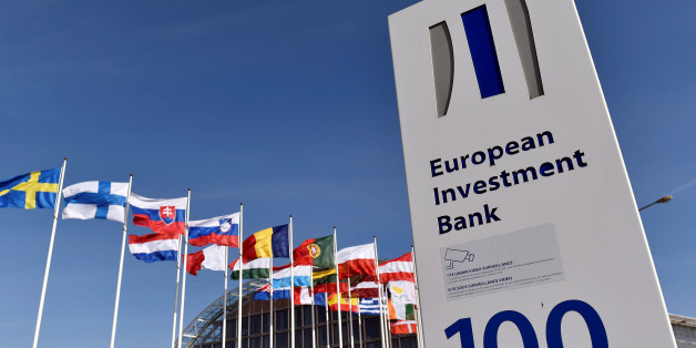 Flags are seen behind the logo of the European Investment Bank is pictured in the city of Luxembourg, Luxembourg, March 25, 2017. Reuters/Eric Vidal