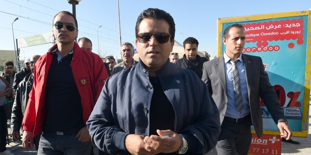 Tunisian presidential candidate and founder of the Free Patriotic Union Slim Riahi (C) arrives at a bus station during a campaign tour on November 19, 2014 in Tunis. Tunisia holds its first multi-candidate presidential election on November 23 in the final stage of a post-revolution transition that has set it apart from the turmoil of other Arab Spring states. AFP PHOTO/FETHI BELAID        (Photo credit should read FETHI BELAID/AFP/Getty Images)