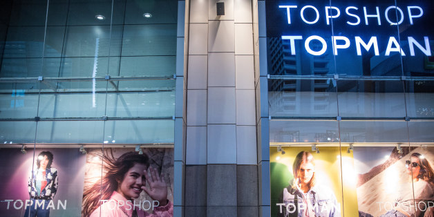 A man uses a smartphone while sitting in front of advertising in the windows of a Topshop store, operated by Arcadia Group Ltd., outside the CentralWorld shopping mall in Bangkok, Thailand, on Wednesday, June 21, 2017. Stocks of consumer discretionary companies -- those that sell products people buy with disposable cash after meeting basic necessities -- have jumped 23 percent in 2017 and are valued 33 percent above their average price-earnings ratio in the past 10 years.Photographer: Taylor Weidman/Bloomberg via Getty Images
