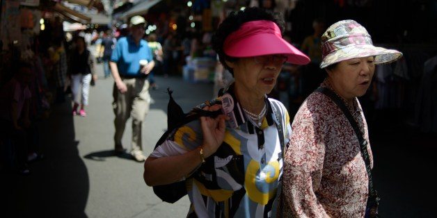Elderly women wearing sun visors walk in a market in Seoul on May 30, 2014. Sun visors are a familiar sight during the summer months in South Korea, which places a high importance on UV protection and skin care. AFP PHOTO / Ed Jones        (Photo credit should read ED JONES/AFP/Getty Images)