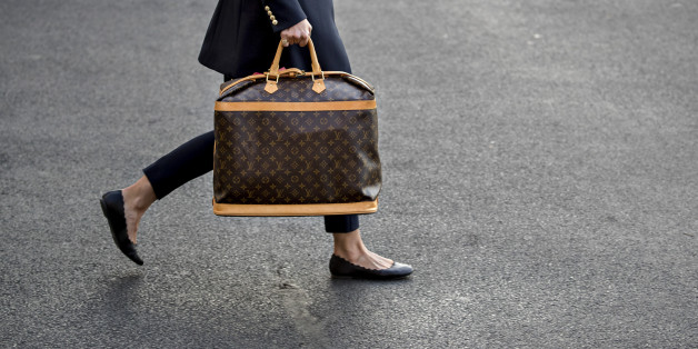 An aide carries a Louis Vuitton handbag to Marine One on the South Lawn of the White House before U.S. President Donald Trump and U.S. First Lady Melania Trump, not pictured, board in Washington, D.C., U.S., on Friday, Nov. 3, 2017. Trump said this morning he doesn't remember much about a March 2016 meeting in which a campaign foreign policy adviser raised the idea of seeking meetings with Russian officials and then continued contacts with Russian intermediaries. Photographer: Andrew Harrer/Bloomberg via Getty Images