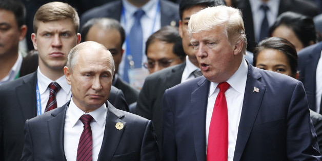 US President Donald Trump (R) and Russia's President Vladimir Putin talk as they make their way to take the 'family photo' during the Asia-Pacific Economic Cooperation (APEC) leaders' summit in the central Vietnamese city of Danang on November 11, 2017.World leaders and senior business figures are gathering in the Vietnamese city of Danang this week for the annual 21-member APEC summit. / AFP PHOTO / POOL / JORGE SILVA        (Photo credit should read JORGE SILVA/AFP/Getty Images)