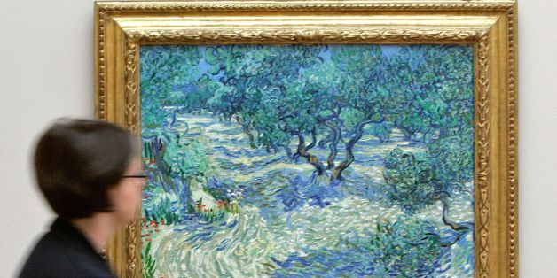 (FILES) File image taken April 23, 2009 shows a visitor looking at the painting 'Olive Trees' (Saint-Remy, June/July 1889) by Dutch artist Vincent van Gogh at the Kunstmuseum in Basel, Switzerland.  It was revealed by a Kansas City art museum on November 7, 2017 that when conservators at The Nelson-Atkins Museum of Art put this Vincent van Gogh painting under the microscope, they found an unlikely intruder: a grasshopper trapped in the canvas's painterly whirls for 128 years. Mary Schafer, a conservator at The Nelson-Atkins Museum of Art, came across the tiny dried, brown carcass in the lower foreground while studying the painting of olive groves. The find reflects the artist's practice of painting in the outdoors, where it was often windy enough to send dust, grass and insects flying.  / AFP PHOTO / NICHOLAS RATZENBOECK / TO GO WITH AFP STORY by Olivia Hampton 'There is a dead bug in the Van Gogh.'        (Photo credit should read NICHOLAS RATZENBOECK/AFP/Getty Images)