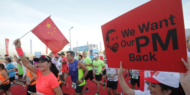 A supporter of Lebanon's resigned prime minister Saad Hariri holds up a placard demanding his return from Saudi Arabia on the starting line of Beirut's annual marathon on November 12, 2017.Hariri announced on November 4 in a televised statement from Riyadh that he would be stepping down from the post, sending shock waves through Lebanese politics. The premier has yet to return to Lebanon and rumours have swirled that he is being held in Saudi Arabia against his will. / AFP PHOTO / ANWAR AMRO