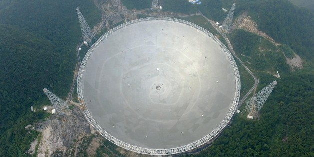 QIANNAN, CHINA - SEPTEMBER 17:  Aerial view of a dish-like radio telescope at Pingtang County on September 17, 2016 in Qiannan Buyei and Miao Autonomous Prefecture, Guizhou Province of China. After five years' construction, 'Five hundred meter Aperture Spherical Telescope' (FAST) will be put into use on September 25. The local public security bureau has intensified security since September 16 in the core zone and around the radio telescope to ensure the radio telescope's completion goes well.  (Photo by VCG/VCG via Getty Images)