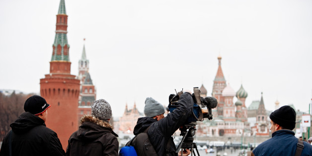 Moscow, Russia - December 10, 2011: TV Reporters installing their camera in front of Red Square on the bridge. Crowds of people walking on Bridge from Red Square and famous St.Basil Cathedral to Bolotnaya square - place of Opposition Demonstration against fraudulent Parliament Elections. Protesters  walking from Red Square to Bolotnaya Square. This Demonstration was organised by opposition parties. Thousands gather at Bolotnaya Square (from 50.000 to 100.000) to protest against election fraud. More than 50.000 police officers were in the center of Moscow this day. This was the biggest protest event for last 20 years in Russia.