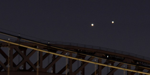 Venus (L) and Jupiter (R) rise together in a rare conjunction over the Hell Gate (rear) and Robert F. Kennedy (front) Bridges in the early morning of August 18, 2014 in New York. The two planets were separated by about 0.25 degrees as viewed from Earth. They will appear farther apart each day but still relatively close together about 45 minutes before sunrise this week. AFP PHOTO/Stan HONDA        (Photo credit should read STAN HONDA/AFP/Getty Images)