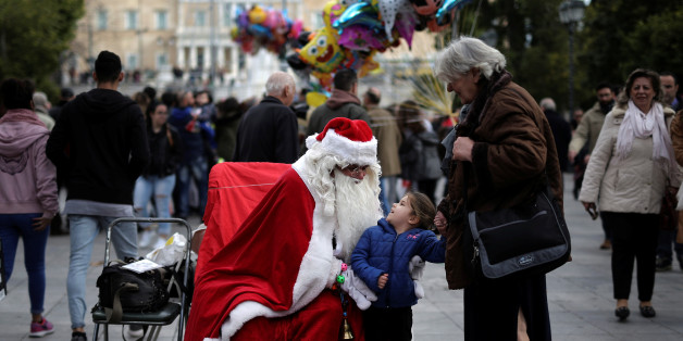 A girl reacts next to a street performer dressed as Santa Claus, on central Syntagma square in Athens, Greece, December 27, 2016. REUTERS/Alkis Konstantinidis