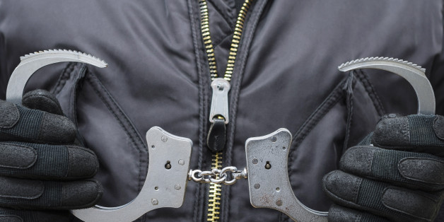 A man in black tactical uniforms holds handcuffs.