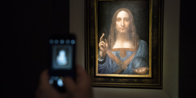 NEW YORK, NY - NOVEMBER 15: A visitor takes a photo of the painting 'Salvator Mundi' by Leonardo da Vinci at Christie's New York Auction House, November 15, 2017 in New York City. The coveted painting is set to be auctioned off on Wednesday night and has been guaranteed to sell for over $100 million.(Drew Angerer/Getty Images)