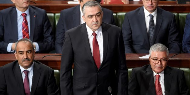 Tunisian nominated interior minister Lotfi Brahem (C) attends a parliamentary session ahead of a vote of confidence in the prime minister's reshuffled government, on September 11, 2017, in Tunis.Tunisian Prime Minister Youssef Chahed on September 6, 2017 announced a major cabinet reshuffle, replacing the key ministers of interior and defence. Three of 11 new faces in the 27-member government served as ministers under the rule of president Zine El Abidine Ben Ali, who was overthrown in Tunisia's