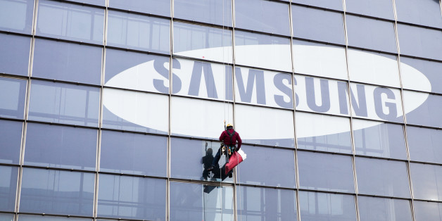 Paris, France - January 20, 2012: A window cleaner coming down from a tall skyscraper with the Samsung logo after the end of his work in the business district.
