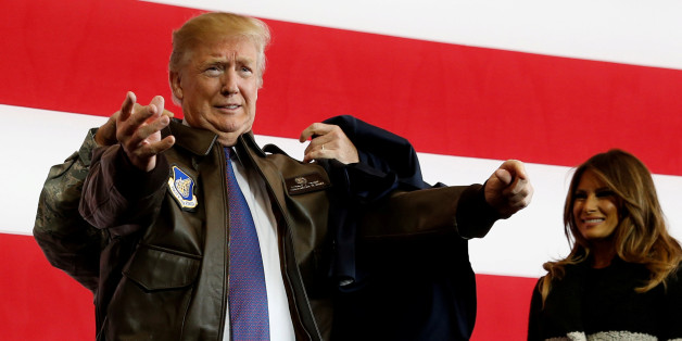 U.S. President Donald Trump puts on a U.S. Pacific Air Forces bomber jacket before delivering remarks to members of the U.S. military at Yokota Air Base, Japan November 5, 2017. REUTERS/Jonathan Ernst     TPX IMAGES OF THE DAY