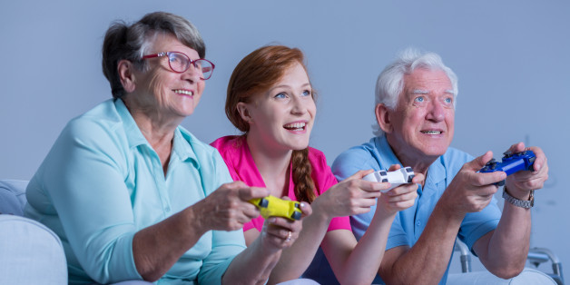Senior people playing video games with young ginger woman