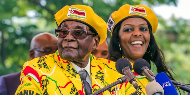 Zimbabwe's President Robert Mugabe (L) addresses party members and supporters gathered at his party headquarters to show support to Grace Mugabe (R) becoming the party's next Vice President after the dismissal of Emerson Mnangagwa November 8 2017.Zimbabwe's sacked vice president, Emmerson Mnangagwa, said on November 8, 2017, he had fled the country, as he issued a direct challenge to long-ruling President Robert Mugabe and his wife Grace. / AFP PHOTO / Jekesai NJIKIZANA        (Photo credit shou