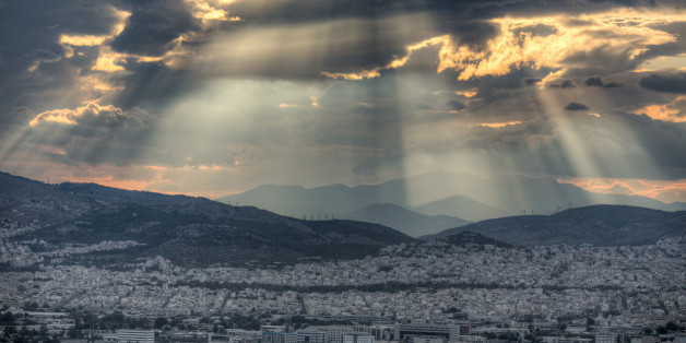 Dramatic sunset with rays of sunlight breaking through dramatic clouds over the city of Athens, Greece.
