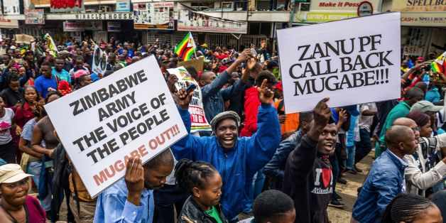 People carry placards during a demonstration demanding the resignation of Zimbabwe's president on November 18, 2017 in Harare.Zimbabwe was set for more political turmoil November 18 with protests planned as veterans of the independence war, activists and ruling party leaders called publicly for President Robert Mugabe to be forced from office. / AFP PHOTO / Jekesai NJIKIZANA        (Photo credit should read JEKESAI NJIKIZANA/AFP/Getty Images)