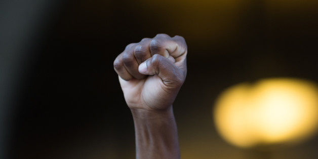 Los Angeles, USA - July 12, 2016 -  Black lives matter protestor put their fists in the air as a sign of 'black power' on City Hall following ruling on LAPD fatal shooting of African American female Redel Jones