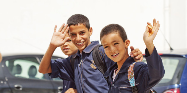 'Nabeul, Tunisia - September 18, 2010: Tunisian school boys are returning to home. They are happy to give a smile to tourists who are taking photos in the streets of Nabeul'