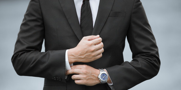 Close up of businessman wearing suit and watch.