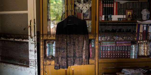 A photo shows a shirt hanging near a bookcase marked with mud from floodwater in a house in Mandra, northwest of Athens, on November 16, 2017, after heavy rainfall caused flooding early on November 15. Greece was in mourning on November 16 as rescue crews tried to locate several people missing in a flood that killed 15 people near the capital, as rain continued to fall. / AFP PHOTO / Angelos Tzortzinis        (Photo credit should read ANGELOS TZORTZINIS/AFP/Getty Images)