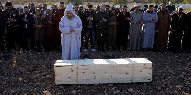 People pray near the coffin of Lakbira Essabiry, one of the people who were killed when a stampede broke out in the southwestern Moroccan town of Sidi Boulaalam as food aid was being distributed in a market, in Sidi Boulaalam, Morocco November 20, 2017. REUTERS/Youssef Boudlal