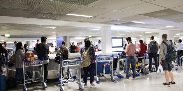 German and foreigner travelers people waiting receive luggage on carousel conveyor at Frankfurt International Airport on August 24, 2017 in Frankfurt, Germany