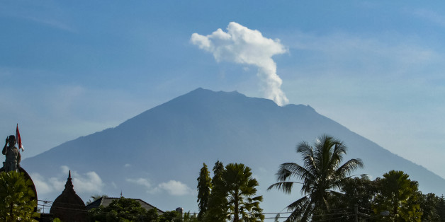 Mount Agung volcano spews steam and smoke into the air as seen from Bangli on Indonesia's resort island of Bali on October 23, 2017.Thousands of residents who fled a rumbling volcano on the island of Bali are refusing to leave evacuation centres after being told to return to their homes outside of the immediate danger zone. / AFP PHOTO / AGUS RANU        (Photo credit should read AGUS RANU/AFP/Getty Images)