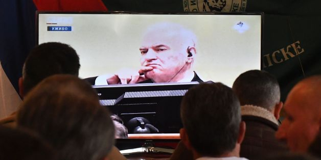 Former Bosnian Serbian commander Ratko Mladic appears on a TV screen wher people gather to watch a live broadcast from the International Criminal Tribunal for the former Yugoslavia (ICTY) on November 22, 2017 in Sokolac as UN judges began handing down their verdict in the trial of Mladic, accused of genocide and war crimes in the brutal Balkans conflicts over two decades ago.  / AFP PHOTO / ELVIS BARUKCIC        (Photo credit should read ELVIS BARUKCIC/AFP/Getty Images)