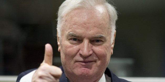 Former Bosnian Serb commander Ratko Mladic thumbs up as he enters the International Criminal Tribunal for the former Yugoslavia (ICTY), on November 22, 2017, to hear the verdict in his genocide trial.Dubbed 'The Butcher of Bosnia,' Mladic's trial is the last before the ICTY, and the judgement has been long awaited by tens of thousands of victims across the bitterly-divided region, seeking to close a chapter in the brutal 1990s Balkans conflicts. / AFP PHOTO / POOL / Peter Dejong        (Photo cr