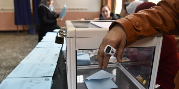 An electoral official stands while an Algerian woman casts her vote at a polling station in Algiers on November 23, 2017 as Algeria goes to the polls for local elections.  / AFP PHOTO / RYAD KRAMDI        (Photo credit should read RYAD KRAMDI/AFP/Getty Images)