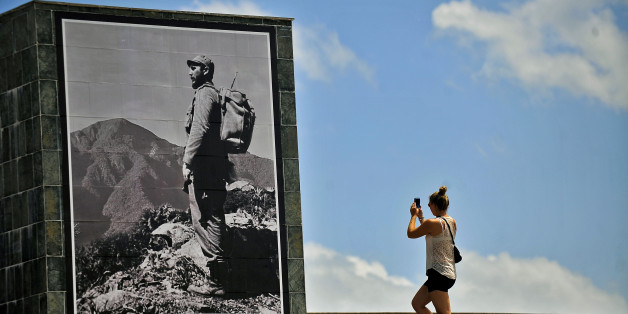 A tourist takes pictures of a poster depicting late Cuban leader Fidel Castro in Santiago de Cuba province on November 23, 2017.Cuba commemorates on November 25 the first anniversary of the death of Fidel Castro, focused on an electoral process that will imply a presidential change, in a framework of economic regression, hostility from the United States, and stagnation in its reforms. / AFP PHOTO / STR        (Photo credit should read STR/AFP/Getty Images)