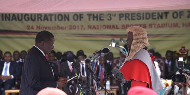 TOPSHOT - Emmerson Mnangagwa (L) is sworn in as the new Zimbabwe's president in Harare, on November 24, 2017 during the Inauguration ceremony. Zimbabwe's ousted vice president was set to be sworn in as president on November 24, 2017, marking the final chapter of a political drama that toppled his predecessor after a military takeover. / AFP PHOTO / Marco Longari        (Photo credit should read MARCO LONGARI/AFP/Getty Images)