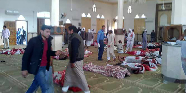Egyptians walk past bodies following a gun and bombing attack at the Rawda mosque, roughly 40 kilometres west of the North Sinai capital of El-Arish, on November 24, 2017.A bomb explosion ripped through the mosque before gunmen opened fire on the worshippers gathered for weekly Friday prayers, officials said. / AFP PHOTO / STRINGER        (Photo credit should read STRINGER/AFP/Getty Images)