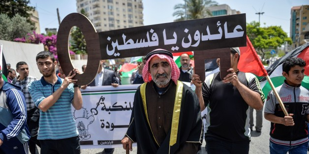 GAZA CITY, GAZA - MAY 15 : Palestinian men hold banners and keys symbolize the Palestinian settlements demolished by Israel Authority during a march marking the 69th anniversary of Nakba, also known as Day of the Catastrophe in 1948, in Gaza City, Gaza, on May 15, 2017. The march demand the rights of Palestinian people to return to their homeland. (Photo by Mustafa Hassona/Anadolu Agency/Getty Images)