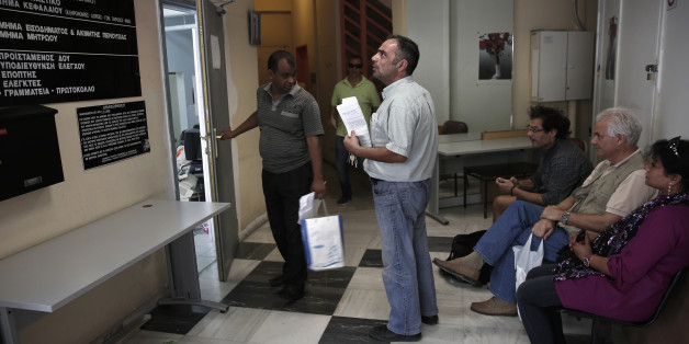 People wait inside a state tax office in central Athens July 2, 2013. Greece has three days to reassure its lenders it can deliver on conditions attached to its international bailout in order to receive the next tranche of aid, four euro zone officials said on Tuesday. There is a general dissatisfaction with progress in Greece when it comes to reforming its public sector, such as tax and custom collection or health care services, a senior euro zone official involved in negotiations said.  REUTERS/Yorgos Karahalis (GREECE - Tags: POLITICS BUSINESS SOCIETY)