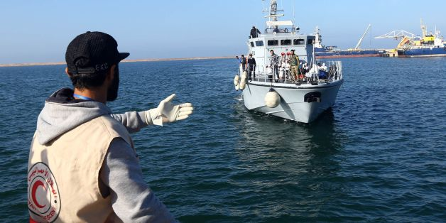 A Libyan Red Crescent worker awaits the arrival of a ship carrying African migrants at a naval base in Tripoli on November 25, 2017, after their rubber boat was rescued off the coast of Garabulli, 60 kilometres (40 miles) east of the capital. More than 30 migrants died and 200 others were rescued when their boats foundered off Libya's western coast, the Libyan navy said.  / AFP PHOTO / MAHMUD TURKIA        (Photo credit should read MAHMUD TURKIA/AFP/Getty Images)