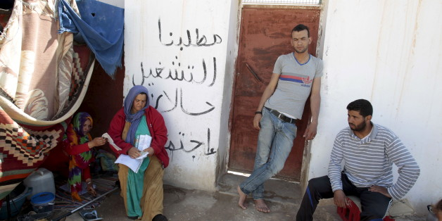 "Protesters are seen near tents in Metlaoui, Tunisia May 11, 2015.  Few shops are open in the Tunisian town of Metlaoui and the local phosphate mine lies idle, blockaded by unemployed young men demanding the government fulfill the economic promises of their country's revolution. Dozens of protest tents are pitched across the rural town with placards calling for ""Dignity"" and ""Work"". REUTERS/Zoubeir Souissi"